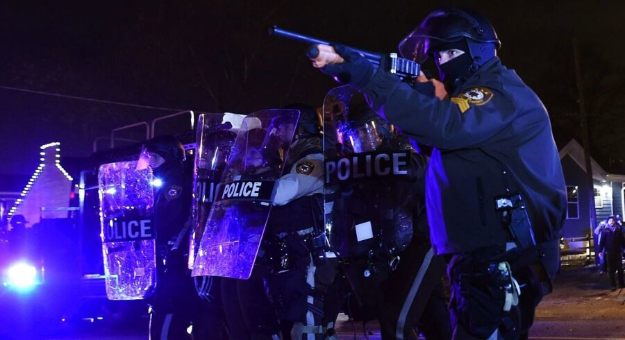 Politiet i fuld udrustning forsøger at neddysse situationen i Ferguson, Missouri.TOPSHOTS Police clash with protesters following the grand jury decision in the death of 18-year-old Michael Brown in Ferguson, Missouri, on November 24, 2014. Protesters set buildings ablaze and looted stores in the US town of Ferguson on November 24 after a grand jury chose not to press charges against a white officer who shot dead a black teen. US President Barack Obama and the family of late 18-year-old Michael Brown appealed in vain for calm after a prosecutor said a grand jury had found the policeman acted in self-defense. AFP PHOTO/Jewel Samad