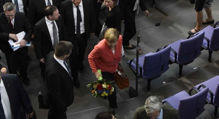 Angela Merkel i den røde jakke fik både fødselsdagsblomster og vandt afstemningen i forbundsdagen om mandatet til at forhandle endnu en hjælpepakke til Grækenland.