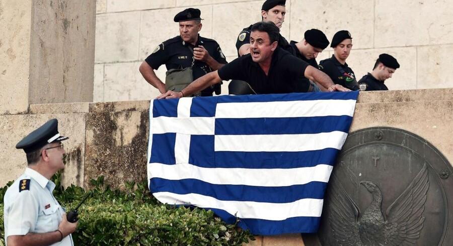 En demonstrant diskuterer med politiet på trappen op til den græske parlamentsbygning i Athen.