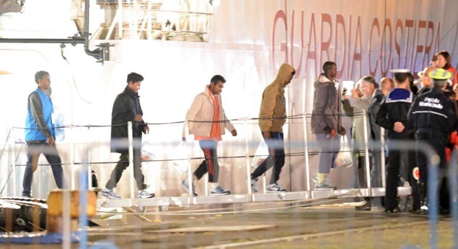 Migranter, der overlevede sejlturen over Middelhavet, går i land fra det italienske kystbevogtningsfartøj Bruno Gregoretti på Sicilien.