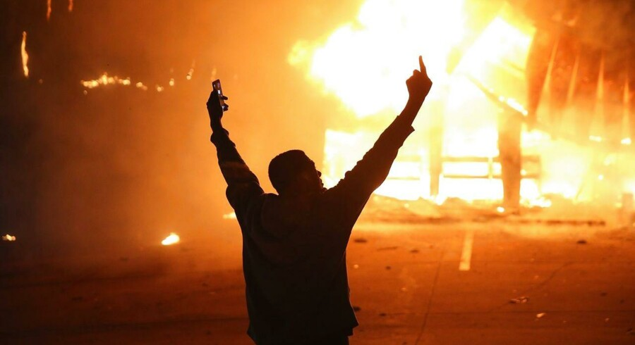 En mand demonstrerer i Ferguson mod storjuryens afgørelse, som siger, at politibetjenten Darren Wilson ikke skal restforfølges for drabet på den sorte teenager Michael Brown.