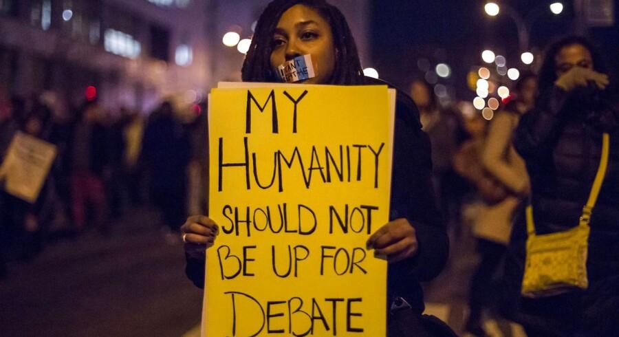 En kvindelig demonstrant kræver retfærdighed for Eric Garner, der måtte lade livet efter en brutal anholdelse.