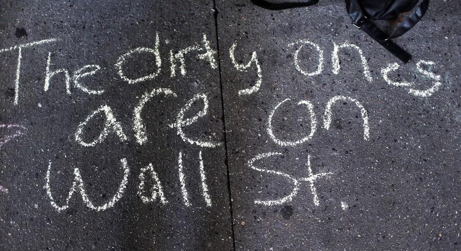 På jorden står med kridt skrevet »De beskidte holder til på Wall Street« med reference til bankerne og finansmogulerne i New York.