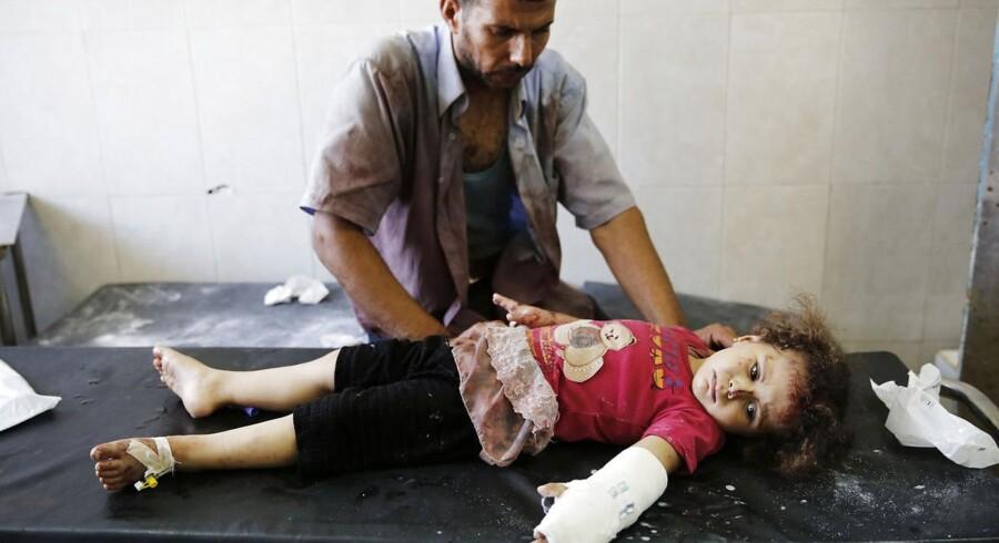 En far trøster sin datter, der ifølge lægerne er blevet såret i en eksplosion i forbindelse med et israelsk angreb.