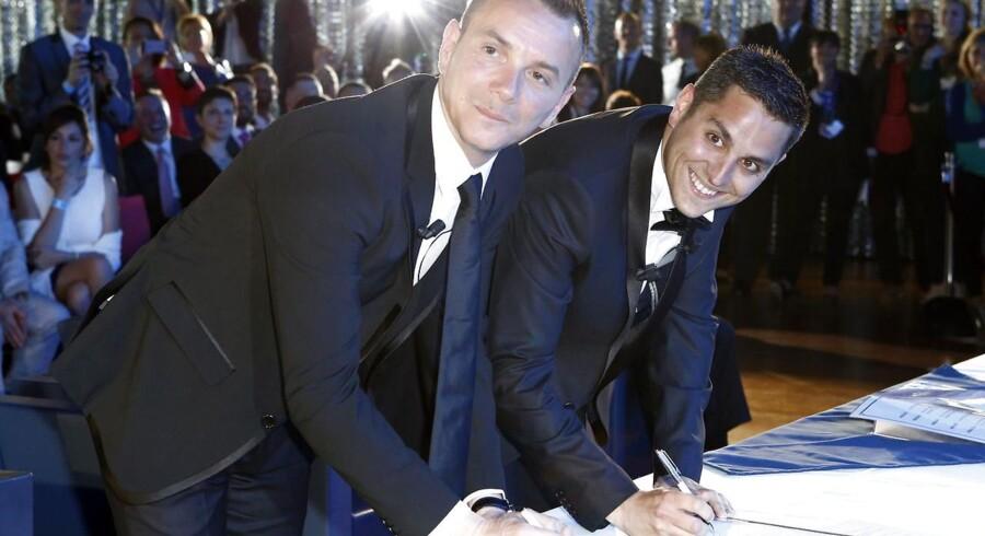 Vincent Autin (til venstre) og Bruno Boileau (til højre) underskriver papirerne på deres ægteskab - Frankrigs første homoseksuelle ægteskab efter lovændringen for nylig. Det skete på rådhuset i den sydfranske by Montpellier. Foto: Arnold Jerocki, EPA/Scanpix