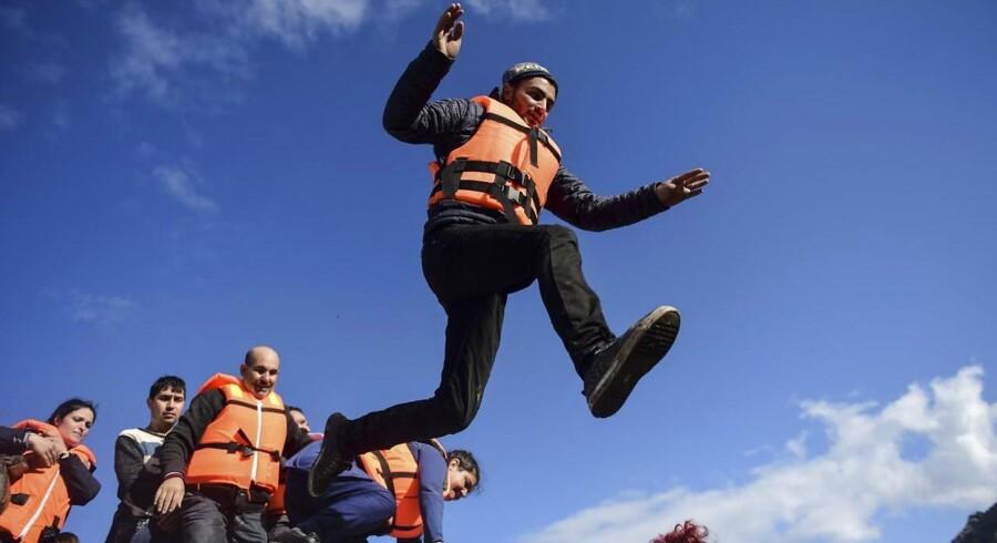 En mand springer i land på den græske ø Lesbos efter at have krydset Det Ægæiske Hav fra Tyrkiet sammen med yderligere en bådfuld flygtninge og migranter.