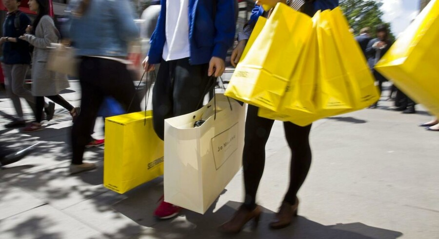 Shoppers carry bags from a Selfridges store as they walk along Oxford Street in central London on May 19, 2015. Britain's annual inflation rate sank into negative territory last month for the first time in move than half a century, official data showed on May 19. AFP PHOTO / JUSTIN TALLIS