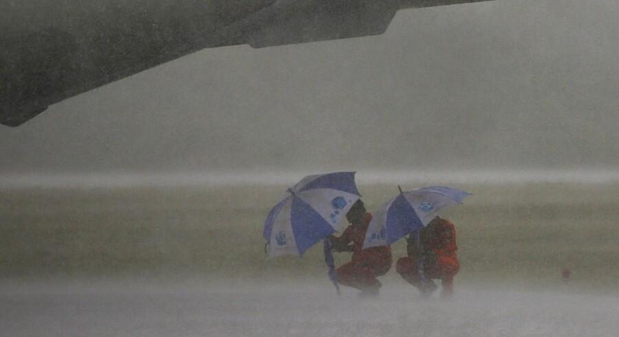 Vejret var den afgørende faktor for det flystyrt, der søndag den 28. december dræbte 162 mennesker. Og det dårlige vejr fortsætter og gør arbejdet med at finde flyvraget svært. To deltagere i eftersøgningen søger her ly for en regnstorm.