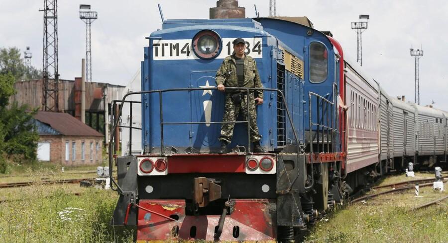En ukrainsk militærmand bevogter det tog, som har fragtet mange af ligene fra MH17-katastrofen til byen Kharkiv.