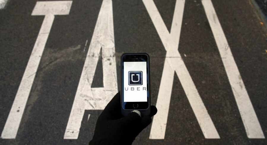 The logo of car-sharing service app Uber on a smartphone over a reserved lane for taxis in a street is seen in this photo illustration taken in Madrid on December 10, 2014. REUTERS/Sergio Perez/Illustration/File Photo