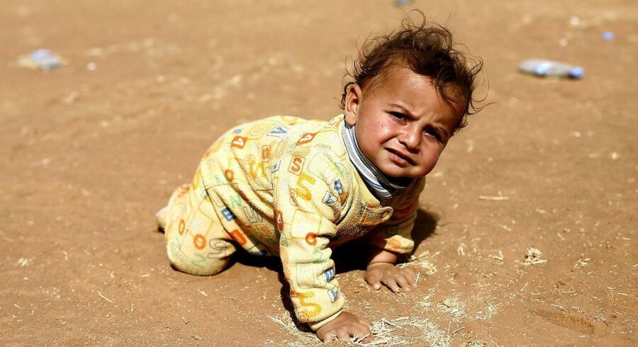 En syrisk baby træner sin kravlekunst i sandet på den tyrkiske side af grænsen til sit krigshærgede og formentlig ukendte hjemland.