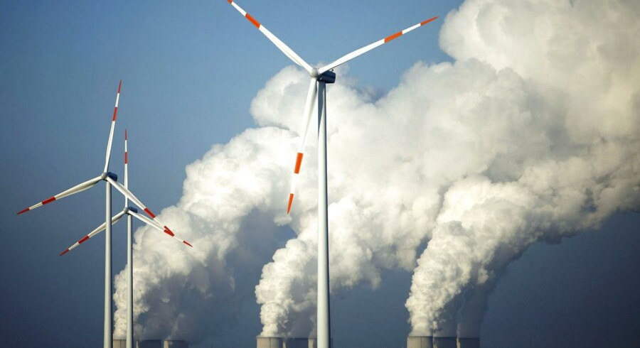 Steam billows from the cooling towers of Vattenfall's Jaenschwalde brown coal power station behind wind turbines near Cottbus, eastern Germany, in this December 2, 2009 file photo.