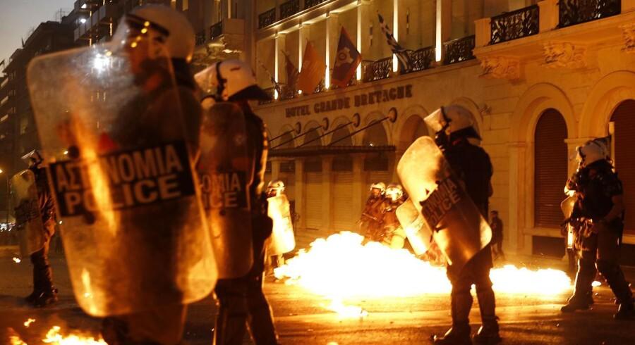 Kampklædte, græske betjente står overfor demonstranter, der kaster med benzinbomber foran det græske parlament i centrum af Athen. REUTERS/Yannis Behrakis