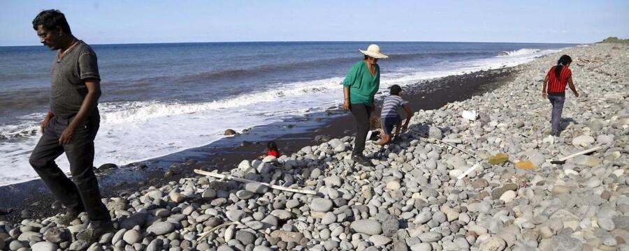 Indbyggere går på stranden på Réunion, hvor et stykke vraggods skyllede op onsdag. I dag skyllede en flydør op på øen.