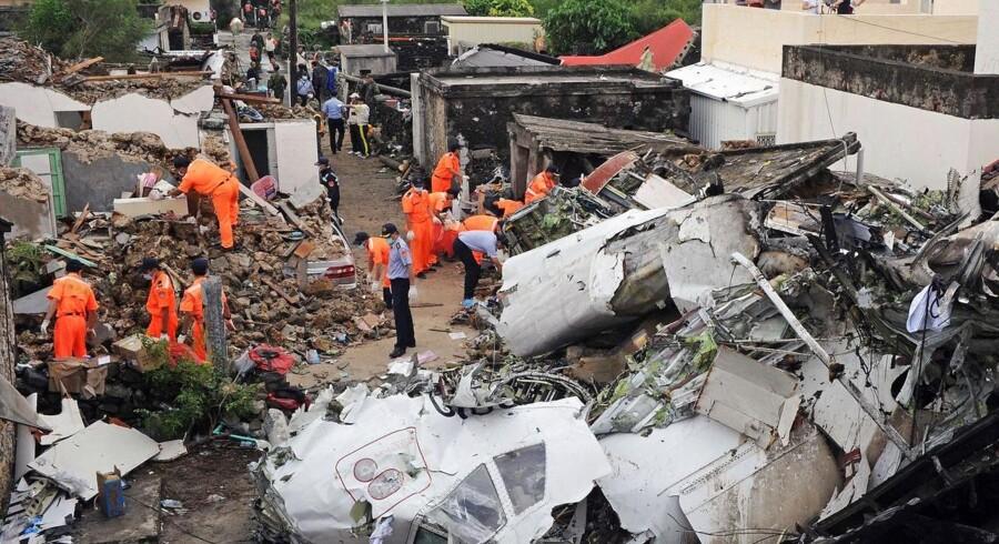 Uhyggeligt mange fly er styrtet ned i 2014. Her er det et billede fra 24. juli i år af et redningshold med brandmænd, der er leder igennem vragdelene fra TransAsia Airways-flyet GE222, som styrtede ned, kort inden det skulle lande near i Magong Lufthavn på Penghu øerne. Få overblikket over årets mange og drabelige flykatastrofer her.