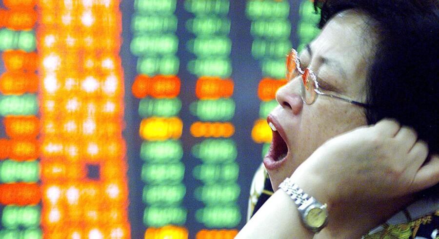 En investor gaber foran en børstavle i Shanghai.
