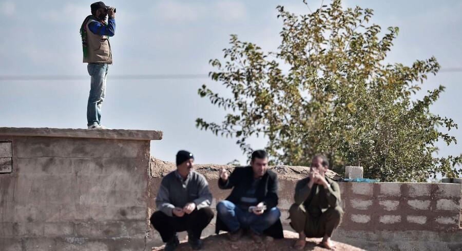 Passet skal kunne inddrages, hvis der er mistanke om, at en person vil rejse til Syrien for at kæmpe, foreslår regeringen. Her betragter kurdiske mænd på den tyrkiske side af grænsen de voldsomme kampe i byen Kobane.