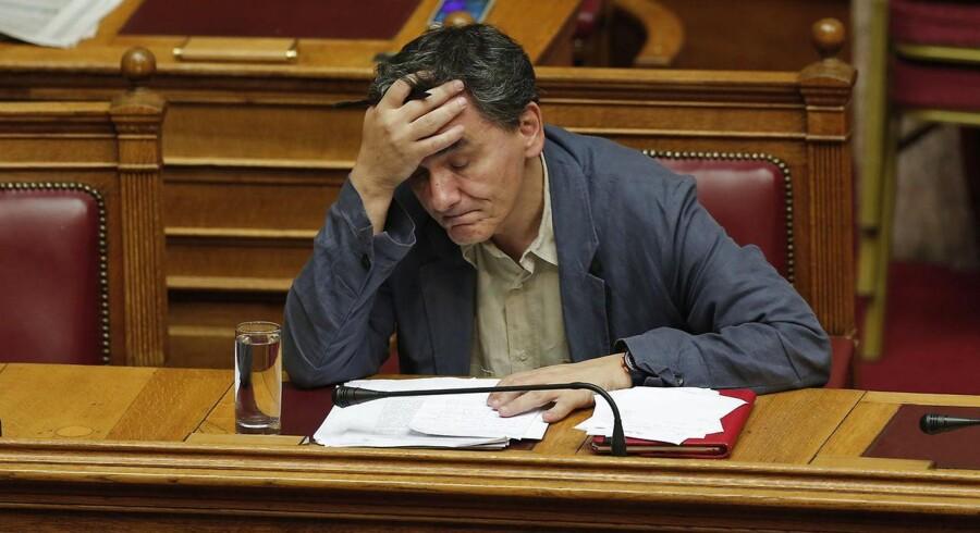 Grækenlands finansminister, Euclid Tsakalotos, tager sig til hovedet under debatten om reformpakken onsdag aften i det græske parlament. Foto: Alkis Konstantinidis