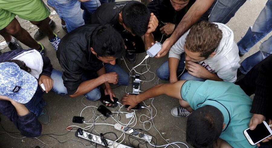 Flygtninge oplader deres mobiltelefoner, mens de venter på at krydse grænsen mellem Grækenland og Makedonien.
