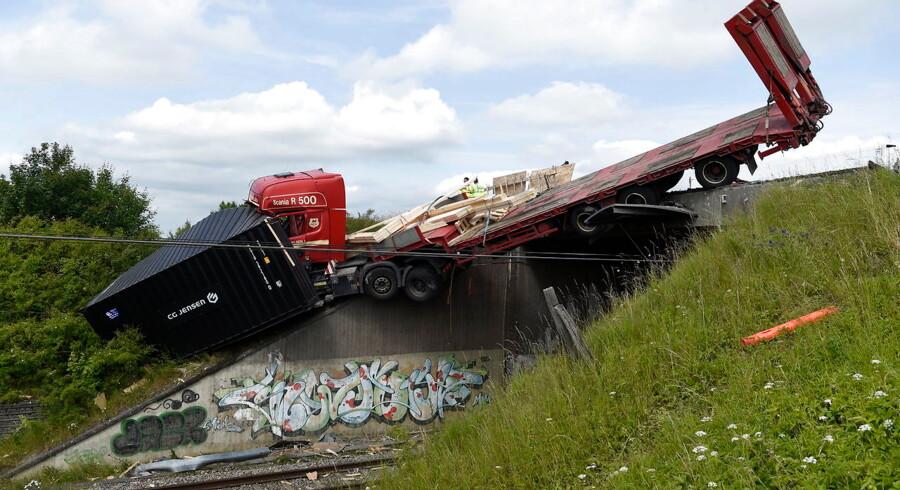 Lastbil kørt ud over bro og stopper togtrafik ved Slagelse Det er uvist, hvorfor en lastbil er kørt galt og havnet delvist på togskinnerne ved Slagelse.