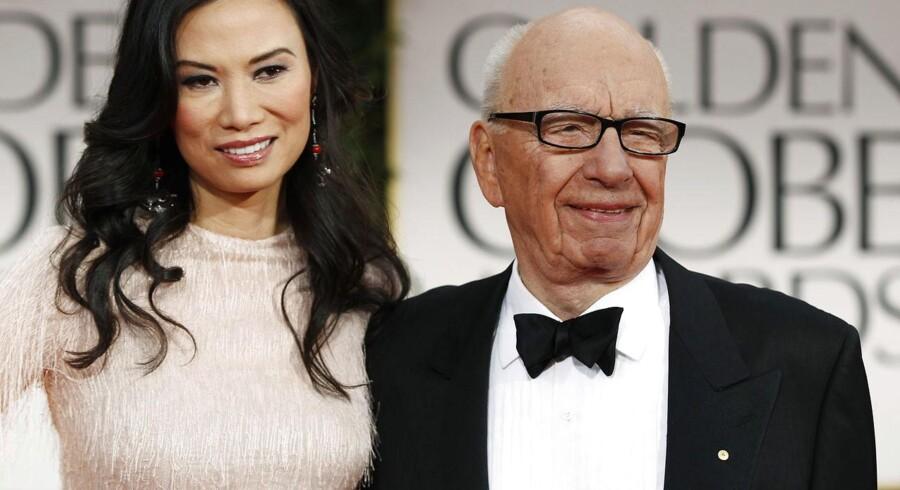 News Corporations ejer Rupert Murdoch smiler sammen med sin kone Wendi Deng ved uddelingen af Golden Globe Awards i Beverly Hills - i hans britiske avisimperium er der knap så meget at grine af.