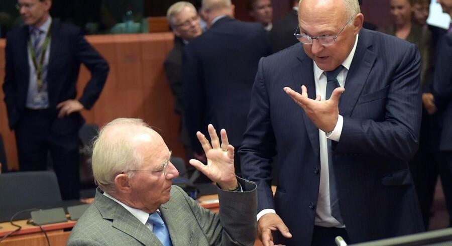 Tysk finansminister Wolfgang Schauble (tv.) og fransk finansminister Michel Sapin ved Eurogruppens ekstraordinære møde omkring Grækenland. Bruxelles, 14. august 2015.