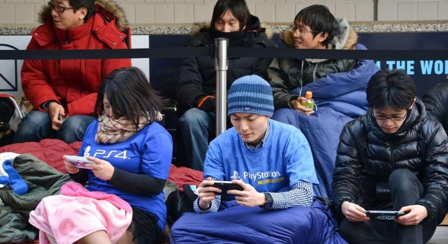 Mange lå i kø i sovepose natten over, da Sony i februar i år begyndte at sælge sin nye Playstation 4-spilkonsol i hjemlandet Japan. Den og konkurrenten fra Microsoft, Xbox One, har trukket spilsalget op men har klemt konkurrenten Nintendo, som nu vil ind på udviklingsmarkederne med en ny konsol fra næste år. Arkivfoto: Kazuhiro Nogi, AFP/Scanpix