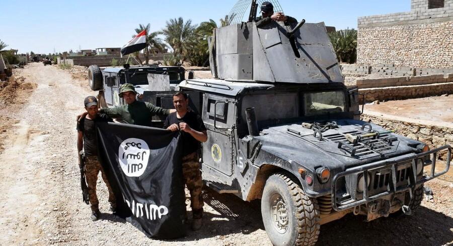 Irakiske tropper holder et IS-flag foran sig, efter de har genvundet kontrollen over landsbyen Al-Mamoura, der ligger nær byen Heet.
