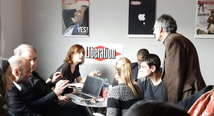 Billede fra avisen Liberations redaktionslokaler, hvor Charlie Hebdo er blevet midlertidigt indkvarteret. Her ses magasinet og avisens journalister og tegnere under et fælles møde fredag.