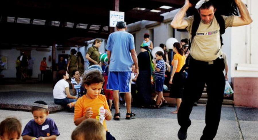 Et soldaterferiested i Ashkelon bliver for øjeblikket brugt som opsamlingssted for bosættere. Børnene bliver underholdt af soldaterne med slik og leg, mens de voksne flytter ind i deres nye, midlertidige hjem. Foto: Scanpix
