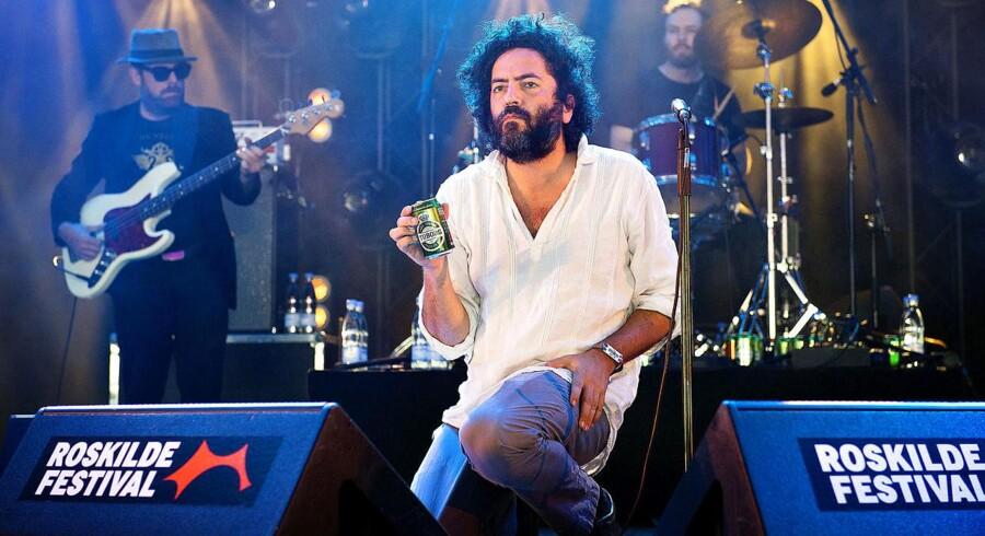 Destroyer optræder på Avalon Scenen torsdag 30 juni på Roskilde Festival. Her er det bandets excentriske frontmand, Dan Bejar, som får sig bajer. Foto: Nils Meilvang