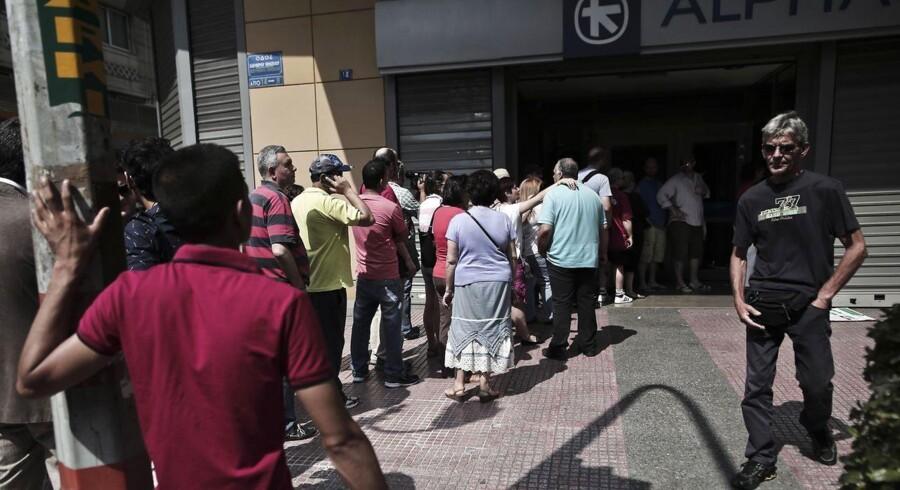 Grækere stod søndag i kø for at hæve kontanter ved en hæveautomat i Athen. Grækenland har nu indført restriktioner på udtræk fra bankerne på 60 euro pr. dag, der som minimum skal løbe frem til folkeafstemningen søndag.