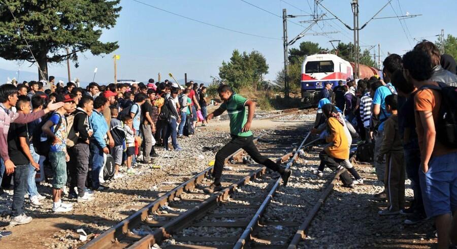 Mennesker der venter på at krydse grænsen til Makedonien, springer over togskinnerne i grænsebyen Idomeni det nordlige Grækenland.