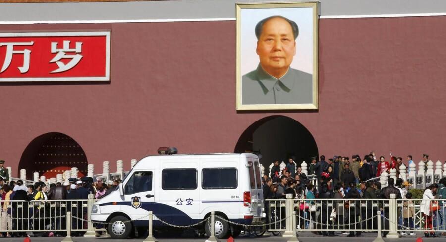 En stor politibil er parkeret foran Den Forbudte By i Beijing, hvor en terrorhandling fandt sted.