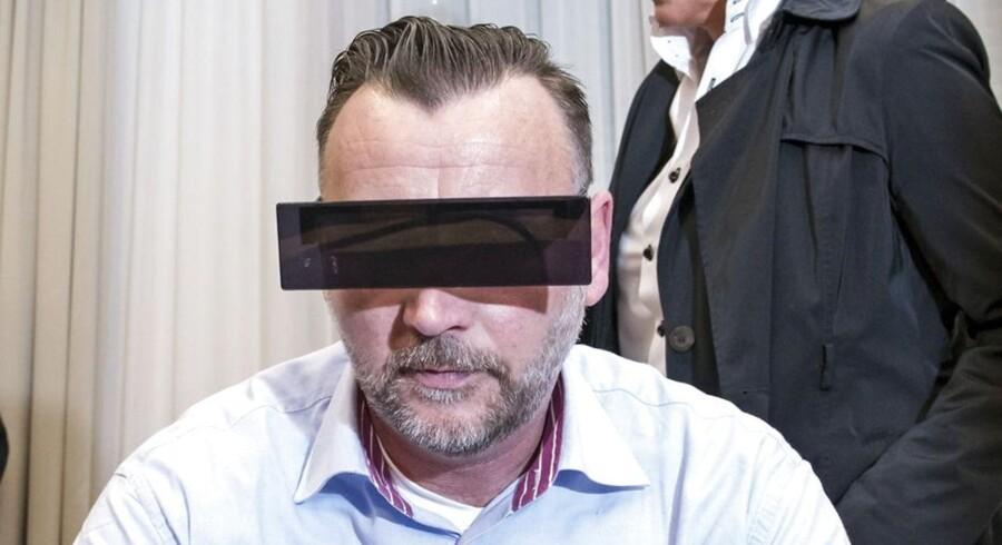 Lutz Bachmann sidder i retten. Han bærer solbriller, der ligner en bjælke over øjnene.