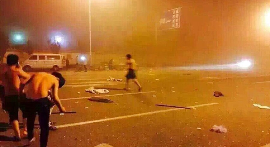 This photo taken with a mobile phone on August 12, 2015 shows people taking shelter on a street after a huge explosion in the northern Chinese port city of Tianjin.
