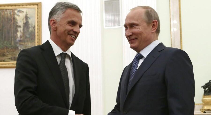 Ruslands præsident Putin giver hånd til den schweiziske præsident Didier Burkhalter ved et møde i Schweiz i maj i OSCE-regi.