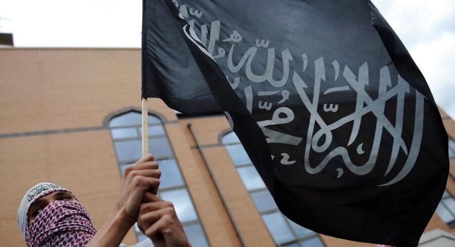 Unge fra Vesten strømmer til Syrien. Her markerer en IS-tilhænger i London sin støtte ved at svinge en islamistisk fane.