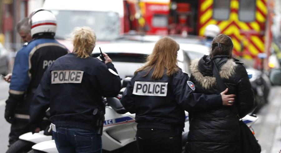 Fransk politi hjælper en kvinde efter skyderierne torsdag morgen i Paris.