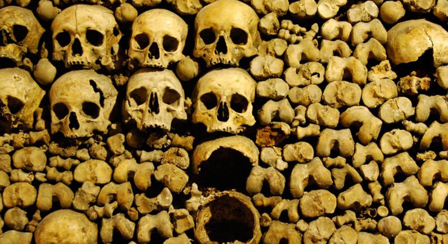 Ben og kranier i millionvis ligger stablet på begge sider ad gangene i Katakomberne i Paris.