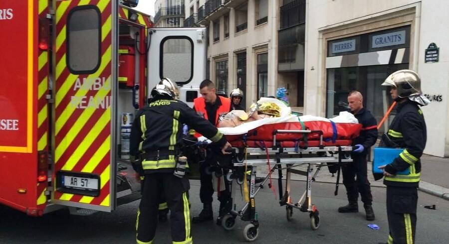 Redningsfolk med en såret mand foran Charlie Hebdo i Paris.