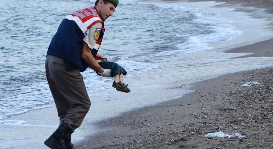 2. september, Tyrkiet.Tyrkisk betjent bærer drengen Aylan Kurdi, der druknede ud for kysten ved Bodrum.Læs også: Et ubærligt billede og Chefredaktør: Derfor bringer vi billede af druknet kurdisk dreng