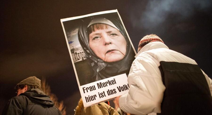 En deltager i en anti-islamistisk demonstration i Dresden holder et skilt med Angela Merkel med tørklæde og med teksten 'Fru Merkel - her er folket'.