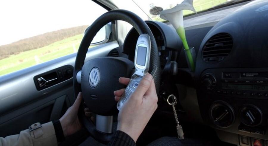 Nej, nej, det er farligt at bruge mobiltelefonen og køre samtidig. Derfor bliver det forbudt også i Illinois i USA. Foto: Colourbox