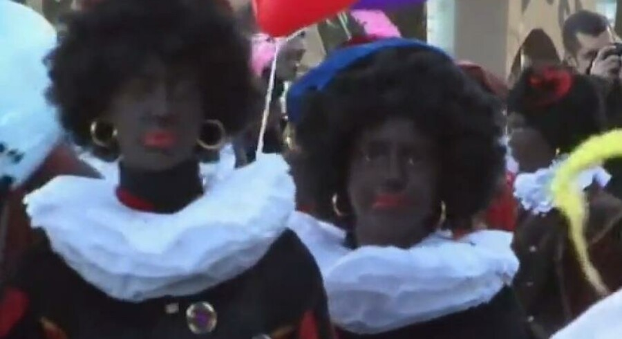 Hollandske skolebørn med kulsort ansigtsmaling, røde læber og sort krøllet paryk for at ligne julemandens hjælper, Zwarte Piet. Screendump: YouTube