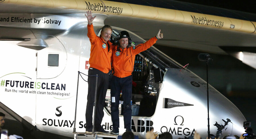 Pilots Andre Borschberg (L) and Bertrand Piccard celebrate after their arrival on Solar Impulse 2, a solar powered plane, at an airport in Abu Dhabi, United Arab Emirates July 26, 2016. REUTERS/Stringer