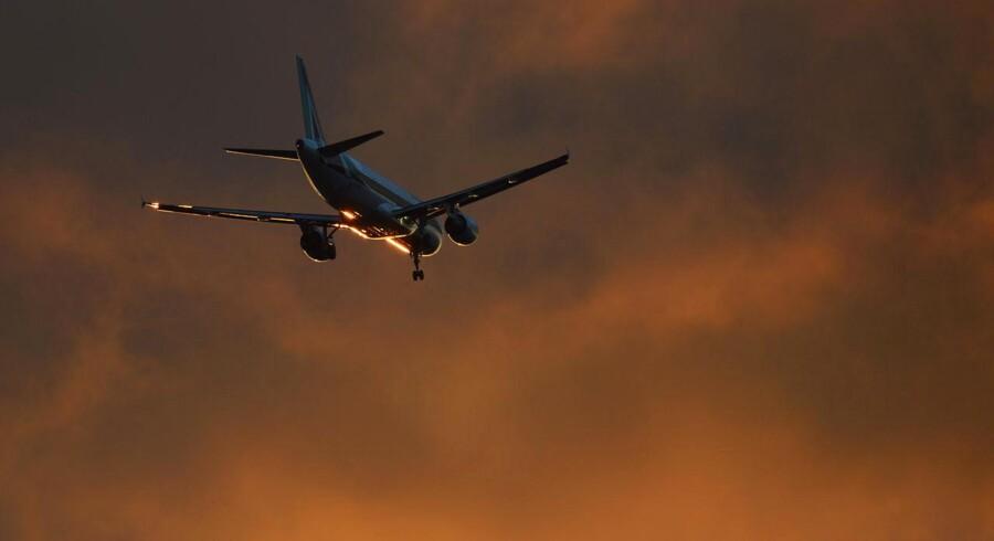 Et fly fra Alitalia på vej til solnedgangs-landing i Heathrow-lufthavnen ved London. Det italienske luftfartsselskab er ikke profitabelt, og nu forsøger det at skaffe friske milliarder, så det kan holde sig på vingerne.