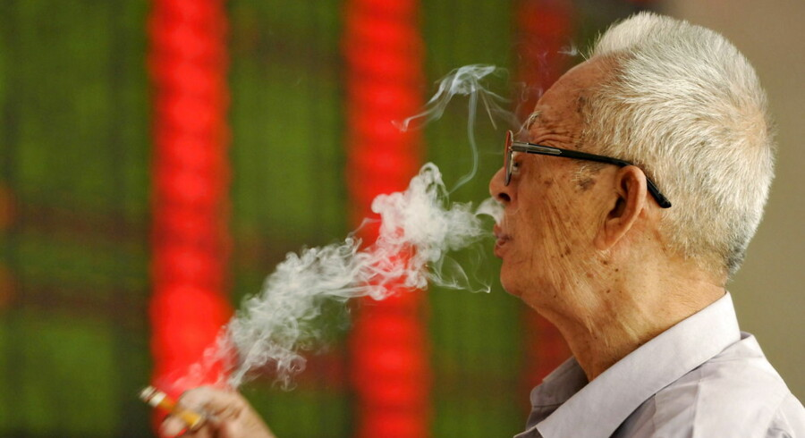 An investor smokes a cigarette in front of an electronic board showing stock information at a brokerage house in Fuyang, Anhui province, China, September 14, 2015. China stocks fell more than 3 percent on Monday morning as lingering concerns over the economy offset optimism that reform among state-owned enterprises (SOEs) would accelerate. REUTERS/Stringer CHINA OUT.NO COMMERCIAL OR EDITORIAL SALES IN CHINA