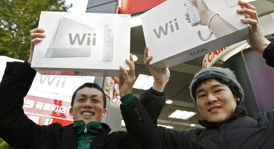 To glade japanere, Masachika Toyama (til venstre) og Yusuke Yano (til højre), sikrede sig en Wii, da den kom i handelen i Tokyo 2. december 2006. Arkivfoto: Kiyoshi Ota, Reuters/Scanpix