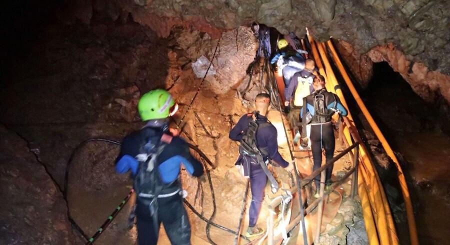 En mindre hær af grottespecialister og militærdykkere arbejder døgnet rundt i forsøget på at redde samtlige drenge ud fra deres langvarige og ufrivillige fængsel omtrent en kilometer under et bjerg i Nordthailand.